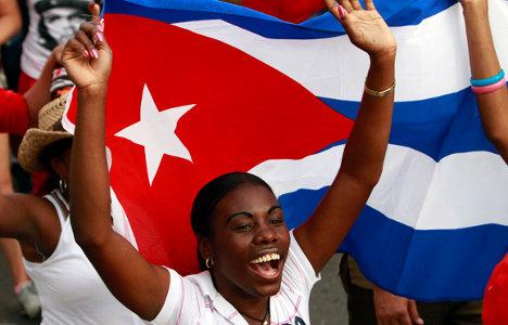 Joven cubana, enarbola la bandera nacional, en una muestra de dignidad y orgullo patrio.
