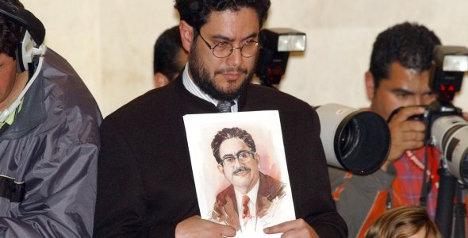 El representante a la Cámara Iván Cepeda sostiene un retrato de su padre asesinado, durante el discurso de los jefes paramilitares ante el Senado colombiano.