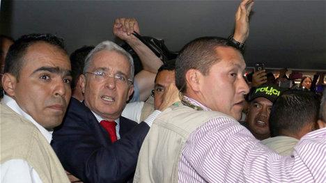Álvaro Uribe sale escoltado del campus universitario.