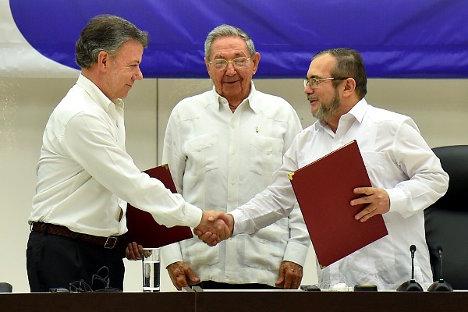 El presidente Juan Manuel Santos y Rodrigo Londoño Echeverry 'Timoleón Jiménez', máximo comandante de las FARC, firman el acuerdo sobre el fin del conflicto en La Habana. Foto: Juan David Tena (Presidencia).