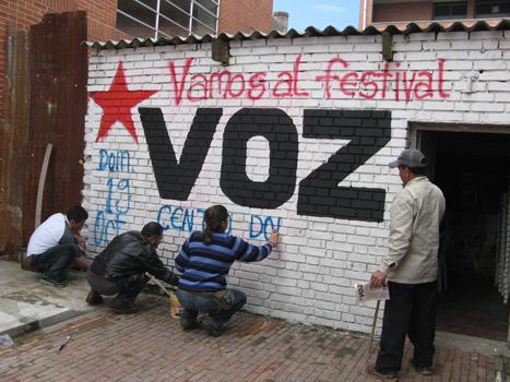 Militantes comunistas pintan mural invitando al Festival de VOZ en Bogotá. Foto archivo.